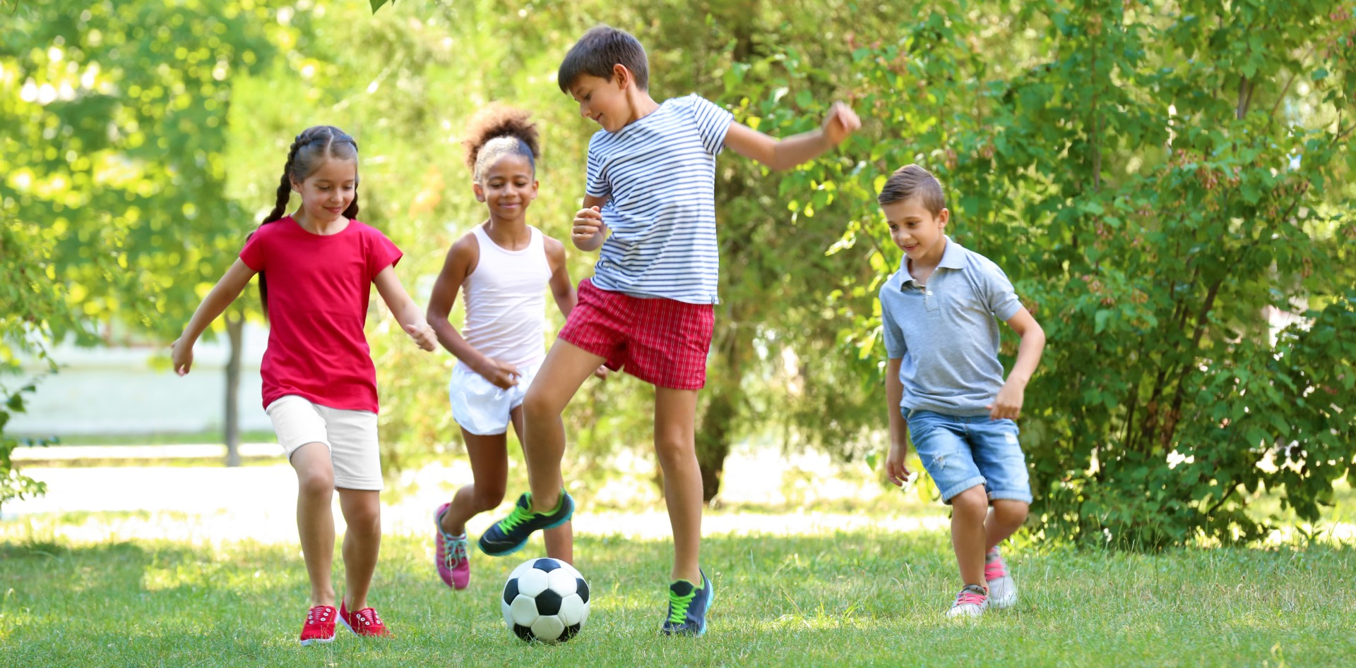 chidren playing football outside - shutterstock