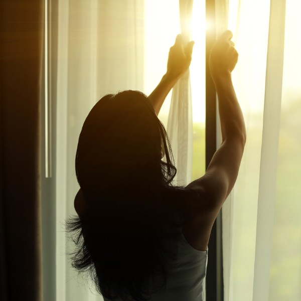 woman closing curtains and windows in the evening