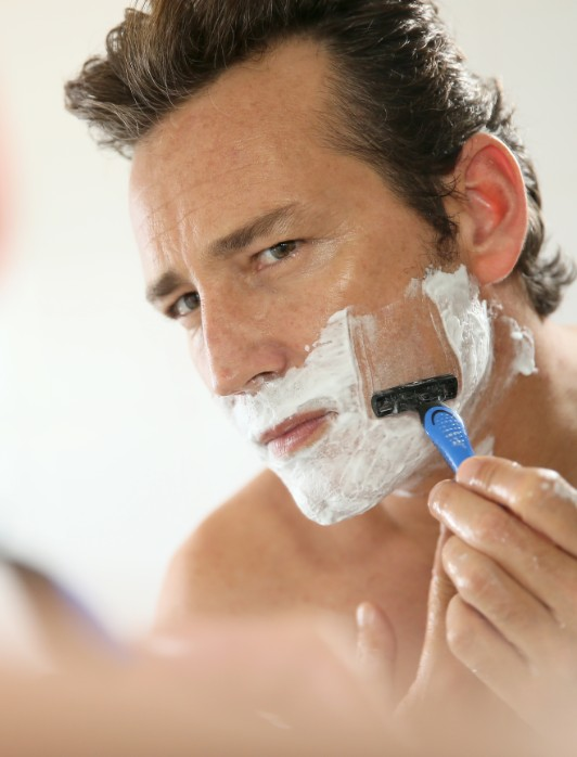 man shaving his face with shaving cream